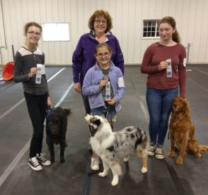 Three 4-H members with their dogs holding their AKC ribbons.